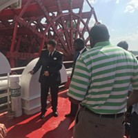 An American Queen official shows off the new USGS sensor installed near the ship's paddlewheel.