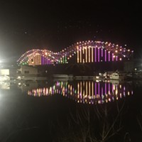 """I didn't realize the Mardi Gras-colored Hernando de Soto Bridge and its reflection created a """"guitar"""" design until I looked at this photo I took on Fat Tuesday. How Memphis can you get? I love when things work out like that."""