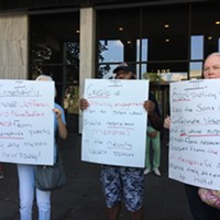Activists hold signs with group's three demands to the City