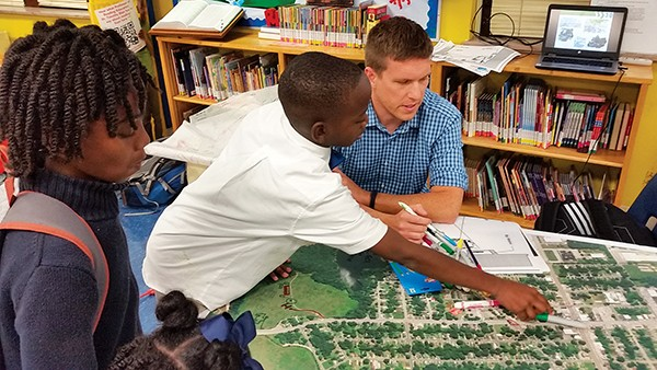 Roger Eckstrom works with local students at Promise Academy to practice making a plan for the city.