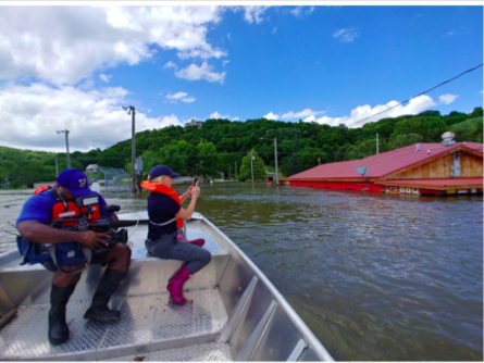 Mayor Rick Eberlin of Grafton, Illinois pilots a boat full of media during a press tour of flooded areas of his city last year. - MISSISSIPPI RIVER CITIES & TOWNS INITIATIVE