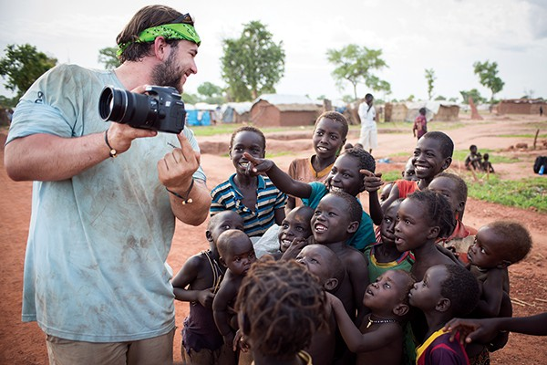 Photographer Jacob Geyer shows a group of children their photograph