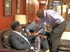 Mayoral candidate Lee Harris, having just got a signature from voter  Cedric Brooks (l), has handed over his petition to Michael Stewart, during a petition-signing party at the Burning Desire Cigar Emporium on HIghway 64