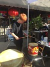 Coltrane Duckworth plays Chinese drums in front of Mulan Bistro.