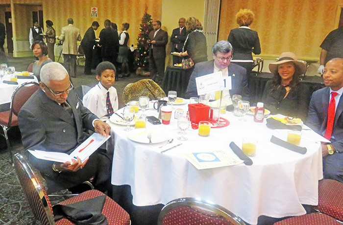 Wharton and Strickland sit uncomfortably at the same table at Myron Lowery's annual prayer breakfast. Others include Mickell Lowery (right) and a deserving young man from the community. - JB