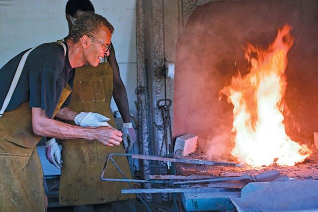 Carl Nielbock and his assistant heat metal at Fort Wayne's 1846 blacksmithing shop. - JUSTIN ROSE