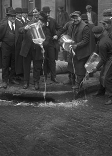 Dumping illegal booze in the gutter after a 1922 raid in New York City.