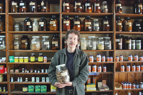 Gary Wanttaja stands before his jars of herbs.