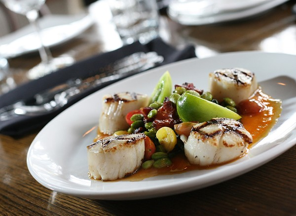 Grilled sea scallops with Swiss chard, tomato, carrot coulis, edamame, bacon lardons and ginger glaze from Detroit Prime.