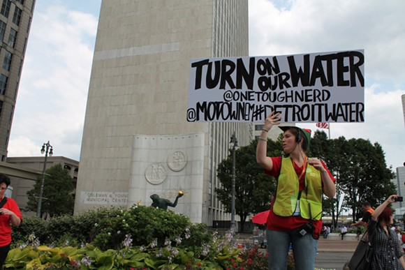 A demonstrator holds a sign during a rally against Detroit's water shut-offs on July 18, 2014. - RYAN FELTON/METRO TIMES