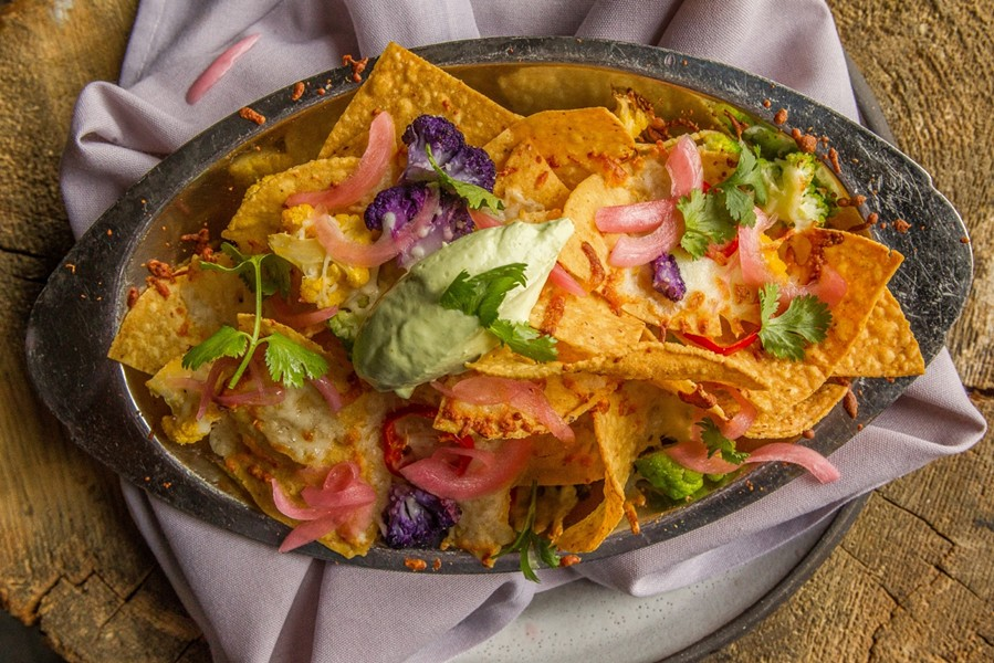 Punch Bowl Social's Cauliflower Nachos are served on a hot skillet, and consist of golden-brown corn tortillas chips topped with a tasty blend of roasted cauliflower, fresh cilantro, fresnos, fried kale, queso fondito and finished with a dollop of jalapeño cream. - PUNCH BOWL SOCIAL