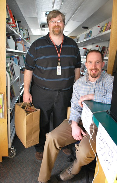 Ryan Boyd, right, and Aaron Jacobsen with his bags full of books inside the bookmobile. - PHOTO: DETROITBLOGGER JOHN