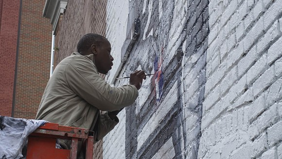 Tylonn J. Sawyer puts the finishing touches on a mural dedicated to Detroit Lions player Reggie Bush late last year. - ANDREW ERDMANS