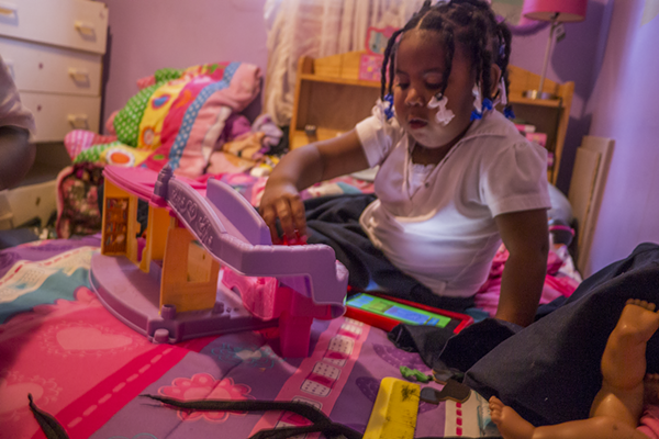 Robertson's daughter Kyi'Lei plays with toys in her bedroom. - IAIN MAITLAND