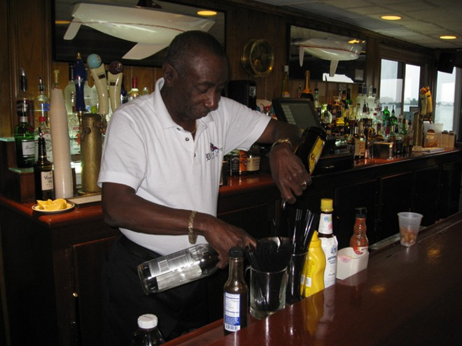 Jerome Adams mixes his signature drink behind the bar at Bayview Yacht Club. - PHOTO BY MICHAEL JACKMAN