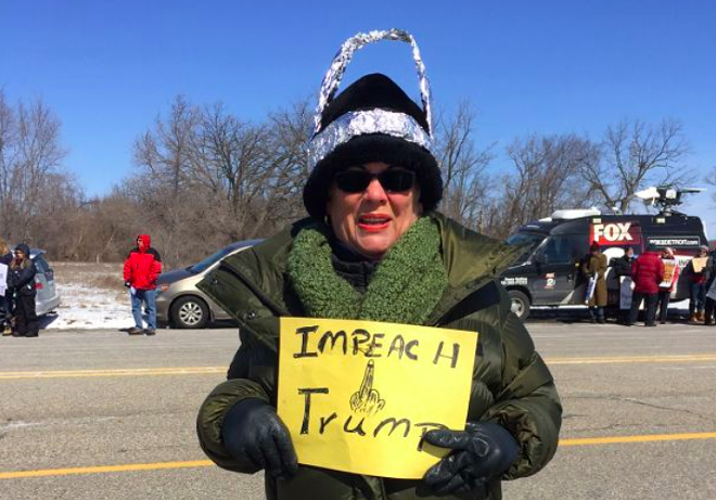 Woman in a tin hat protesting Trump's visit to Ypsilanti last year. - VIOLET IKONOMOVA