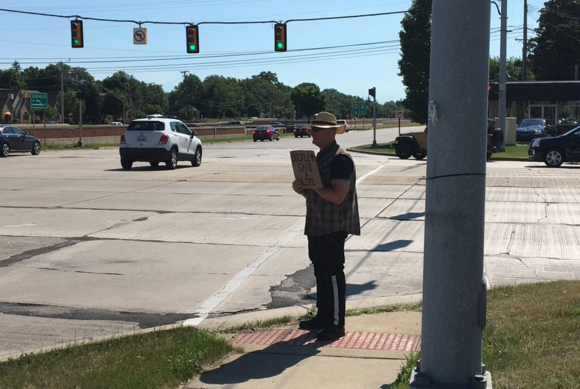 An MSP trooper poses as what very much resembles a panhandler at the intersection of Southfield Road and I-696 on Tuesday. - TWITTER, @MSPMETRODETROIT