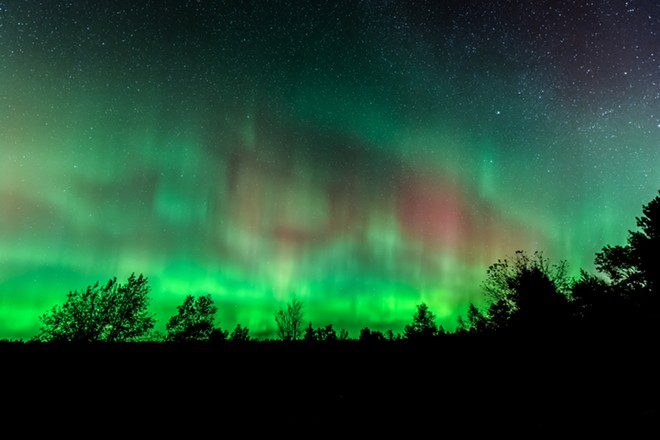 Northern Lights over Benzie County Michigan wooded area. - VIA SHUTTERSTOCK