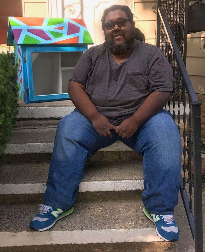 James Chism, Harper Woods resident and participating artist in the Little Library prize, sits with the library he painted, called Breaking Barriers, Smashing Ceilings. - COURTESY OF JAMES CHISM
