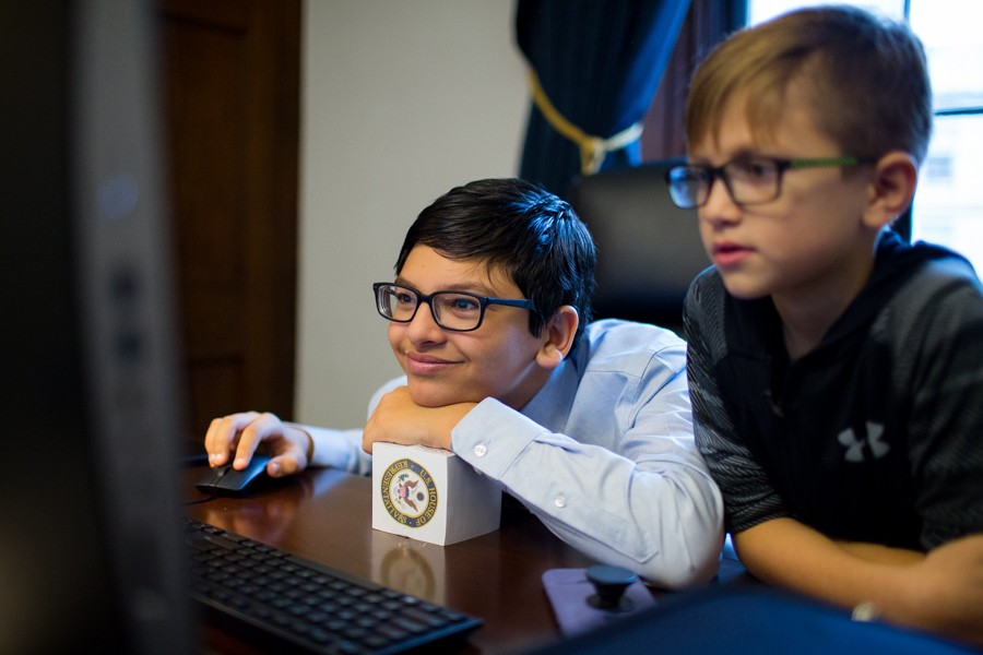 Tlaib's son, Adam, reads the day's news on his mother's newly set up computer in her office. - ERIK PAUL HOWARD