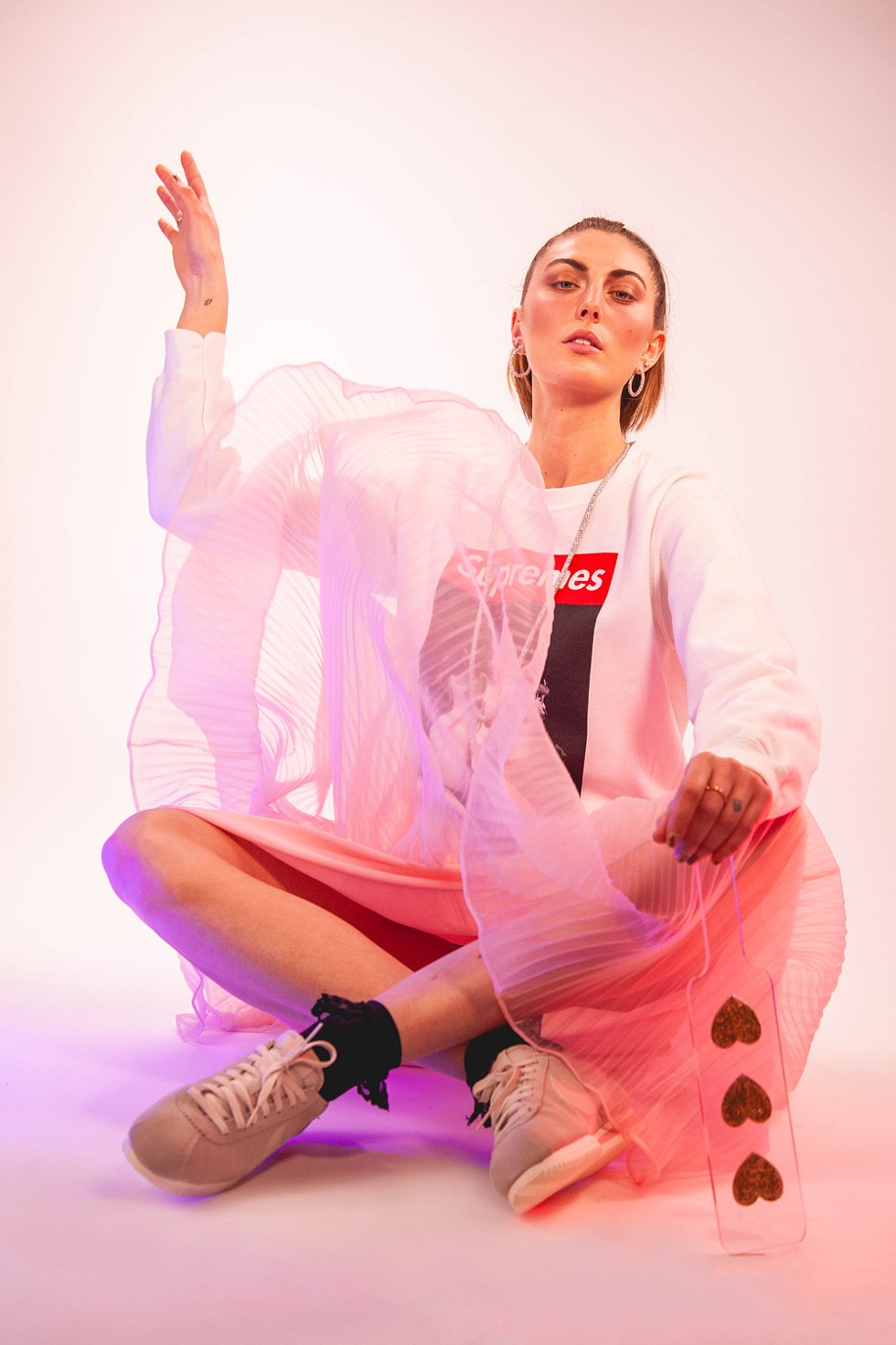 Impact play: Supremes crewneck sweatshirt, $60, SMFLD, 313-285-9564, buy.smplfd.com; Cortez sneakers, Nike, $90, 313-965-3319, nike.com; Pink Dream dress, $68, Shop Minnie Lou, @shopminnielou, 1418 Michigan Ave., Detroit; black ankle socks, $4.50, 248-541-3979; noirleather.com; diamond necklace, $27,000, hoop earrings, $999.99, pink studs, $1,499, multi-colored ring, $1,599, New World Diamonds, newworlddiamonds.com; heart paddle, $42, eatdarich.com. - MILES MARIE OF NOMADIC MADAM