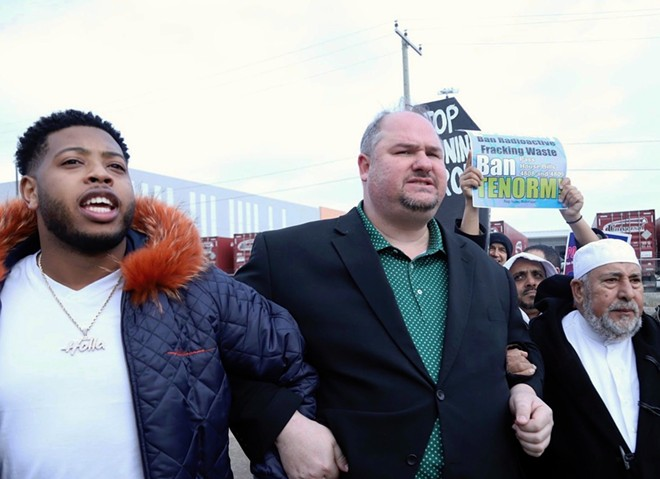 State Rep. Isaac Robinson (center) locks arms with state Rep. Jewell Jones (left) and Imam Salah Algahim (right) as they march from a nearby school to US Ecology on Detroit's east side. - STATE REP. ISAAC ROBINSON
