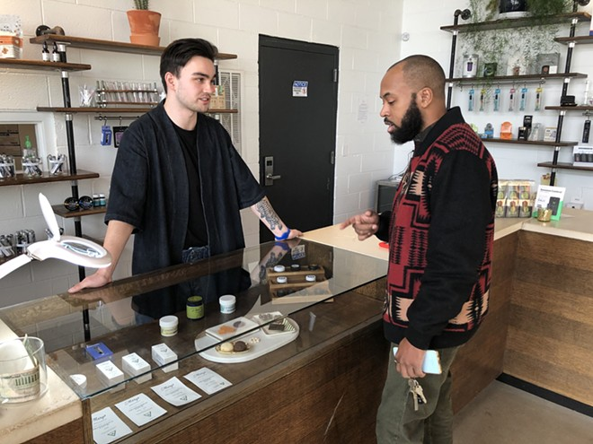 A budtender helps a customer at Detroit's BotaniQ. - LEE DEVITO