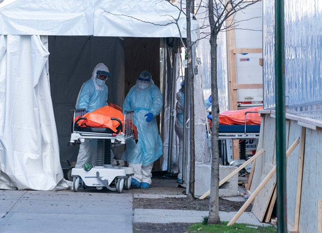 Body of deceased patient in orange bag moved from hospital to refrigerator truck serving as temporary morgue outside of Wyckoff Heights Medical Center in Brooklyn. - SHUTTERSTOCK.COM