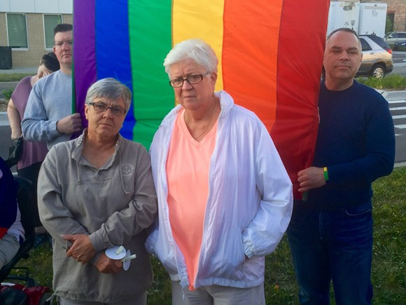Rose O'Day, 62, left, with wife Kathy Huebener, 71, at a Sunday vigil at Ferndale City Hall for mass shooting victims in Orlando. A couple for 25 years, the Warren women married in October after same-sex marriage became legal in Michigan. - PHOTO BY DUSTIN BLITCHOK.