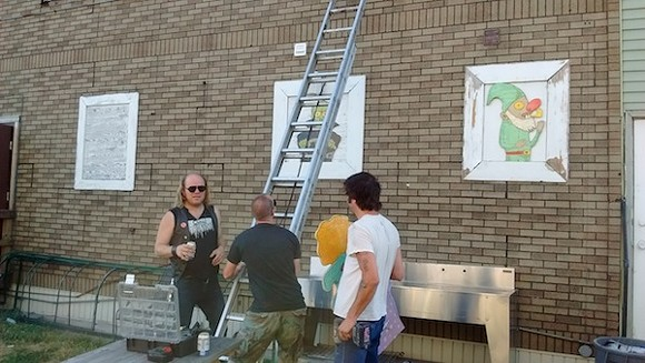 Lampinen (left) and Easter (right) get ready to adorn a wall with more art. - PHOTO BY MICHAEL JACKMAN