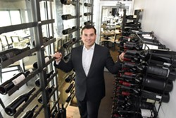 Aaron Belen stands among the wine racks at Bistro 82. - PHOTO BY VAUGHN GURGANIAN