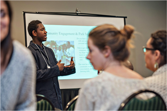 Chad Segrist's student Davaughn Smith presenting at the 2016 Annual SEMIS Community Forum about work he and other DIT students are doing to design a park on the former site of an abandoned building across the street from the school. The students worked with the city to get the building demolished. - PHOTO BY LEISA THOMPSON. COURTESY OF THE SEMIS COALITION.