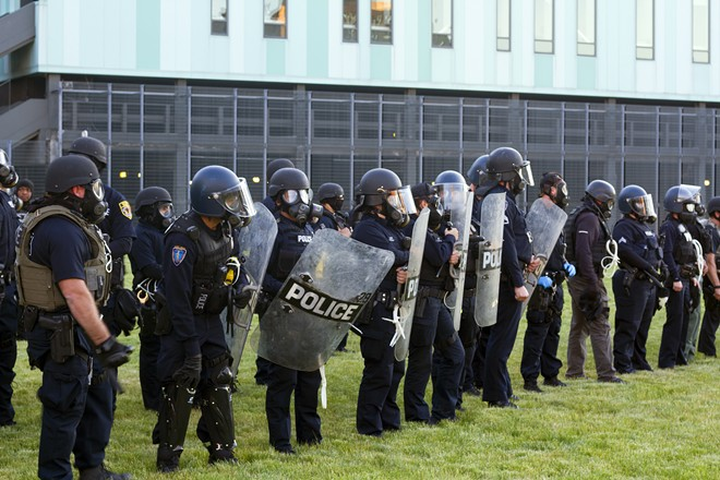 Detroit police lined up with helmets and shields before enforcing the curfew Sunday. - STEVE NEAVLING