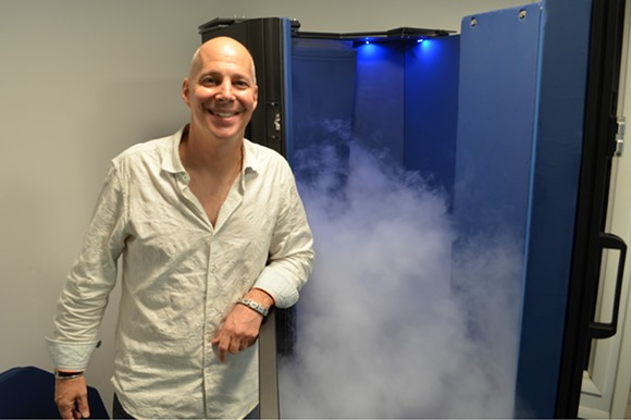 Eric Spector with the cryotherapy chamber at CryoWorks Michigan in Berkley. - PHOTO BY DUSTIN BLITCHOK
