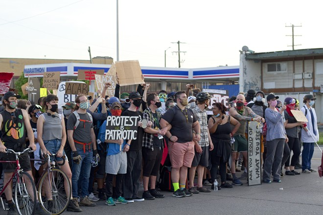 Protesters locked arms as Detroit police in riot gear approached to enforce the curfew. - STEVE NEAVLING