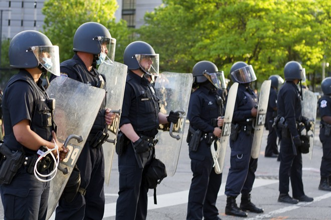 Detroit police formed a line before firing tear gas, flash-bang grenades, and rubber bullets at peaceful protesters to enforce a curfew. - STEVE NEAVLING