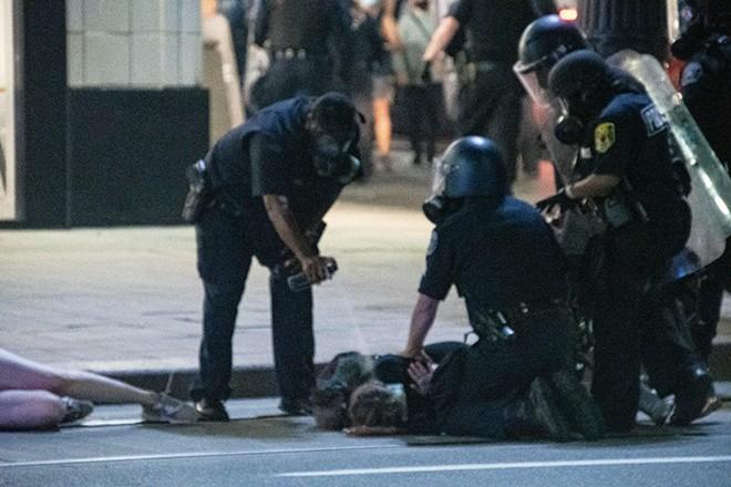 Police use pepper spray on a protester on Aug. 23. - ADAM DEWEY