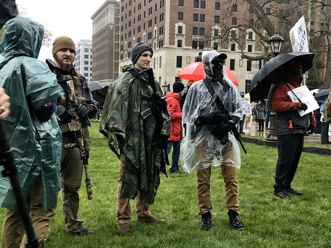 Protesters with rifles outside the state Capitol - STEVE NEAVLING