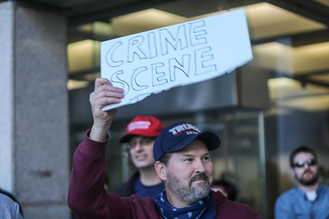 A Trump supporter wielding a sign alleging voter fraud outside of Detroit's TCF Center. - RUSTY YOUNG
