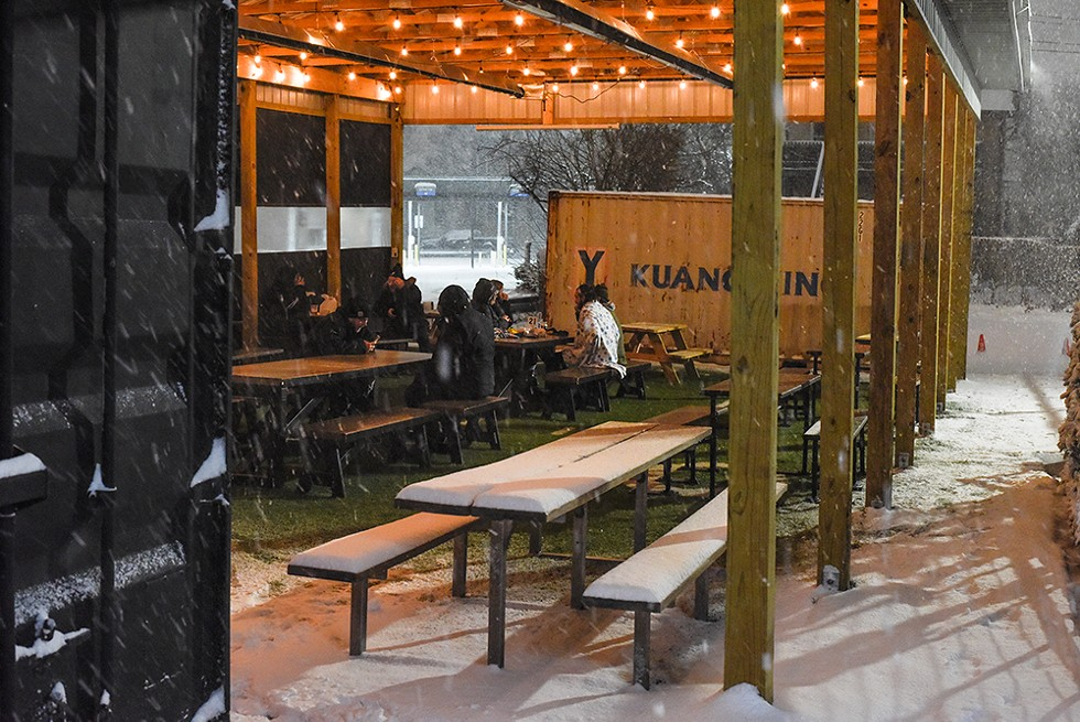 "Guests drink beers under Batch Brewing Co.'s ""Fauci Fieldhouse"" outdoor pavilion. The company has decided not to reopen for indoor dining until more people get vaccinated. - KELLEY O'NEILL"