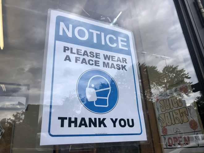 A sign at the Detroit Whole Foods asks customers to wear a face mask. - STEVE NEAVLING