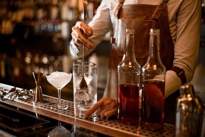 A bartender makes cocktails. - SHUTTERSTOCK.COM