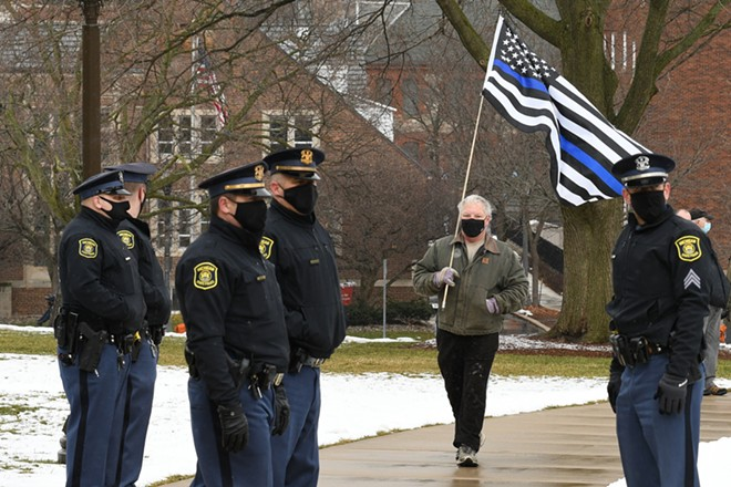 """Man carrying a """"blue line"""" flag signifying support for police on the lawn of the Michigan Capitol. - LESTER GRAHAM / SHUTTERSTOCK.COM"""