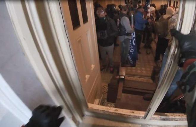 Screenshot of GoPro video of Anthony Michael Puma crawling through a broken window at the U.S. Capitol on Jan. 6. - FBI