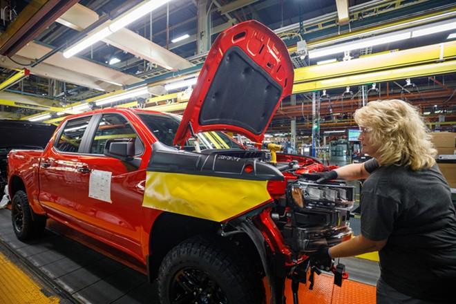 A worker installs a headlight assembly at GM's Chevrolet Silverado and GMC Sierra pickup truck plant. - JOHN GRESS MEDIA INC / SHUTTERSTOCK.COM