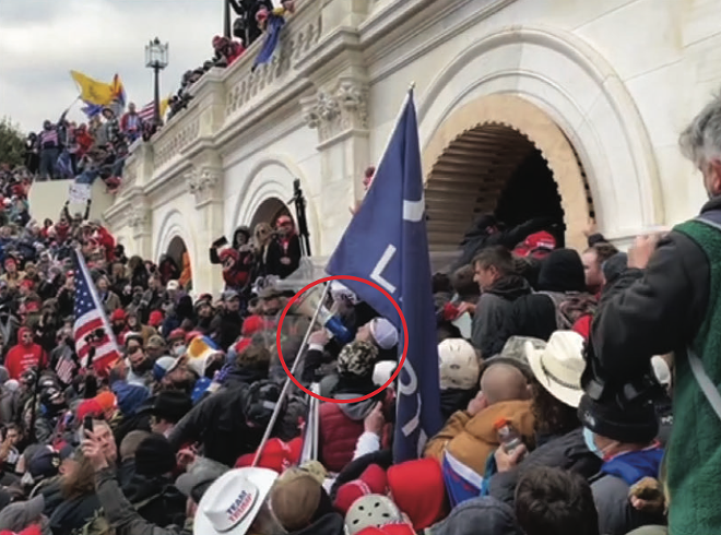 Trevor Brown is circled in red near the front of a violent crowd that was trying to push past police officers at a tunnel at the U.S. Capitol. - FBI