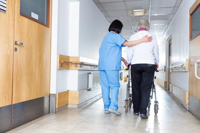 A nurse and an elderly patient. - SHUTTERSTOCK