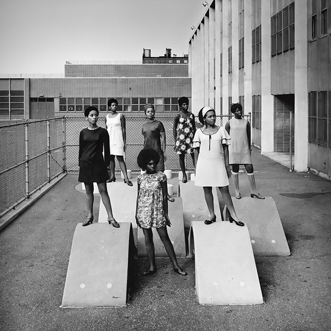 Kwame Brathwaite, Photo shoot at a public school for one of the AJASS-associated modeling groups that emulated the Grandassa Models and began to embrace natural hairstyles. Harlem, ca. 1966; from Kwame Brathwaite: Black Is Beautiful (Aperture, 2019). - COURTESY OF THE DIA