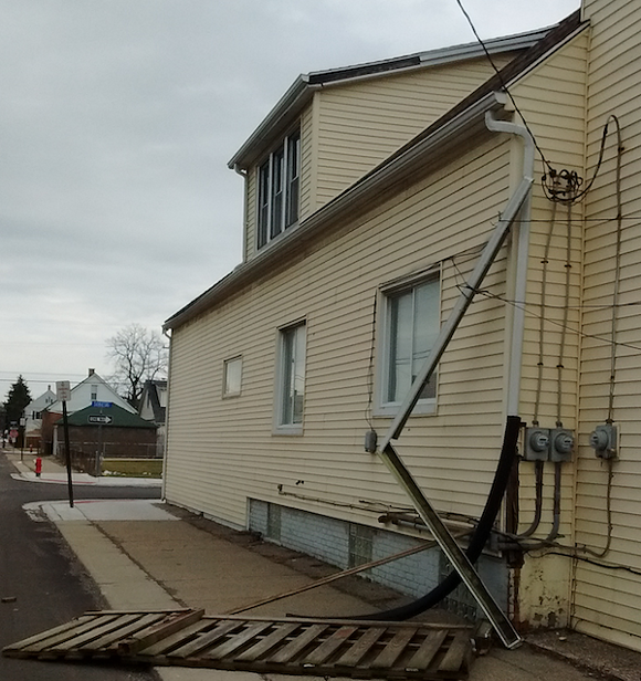 Wind caused gutter damage to this Hamtramck home, as well as taking out a few sections of fence. - PHOTO BY MICHAEL JACKMAN