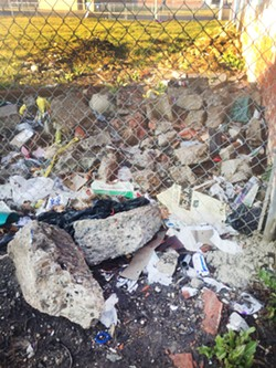 Trash and construction debris on a vacant Velleman-owned lot.